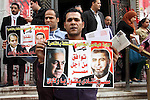 """Egyptian street vendors hold portraits read in Arabic """"Unite and save Egypt"""" during a protest in front of High Court against the curbed by the police eviction policies that threaten to terminate their small businesses at any time, in Cairo on march 07, 2013. Photo by Tareq al-Gabas"""