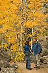 Couple standing on trail through the golden colors of autumn in aspen stands above Bear Lake on a September morning in Rocky Mountain NP, Colorado/ (MR)#86