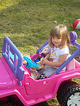 Toddler in electric fisher-price toy jeep with dolls.