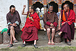 Farmers in sandals and Buddhist monks strangely in shoes. A traditional Puja celebration, a yearly Buddhist festival by the local community, Chuchizshey temple, Bumthang, Bhutan..Bhutan the country that prides itself on the development of 'Gross National Happiness' rather than GNP. This attitude pervades education, government, proclamations by royalty and politicians alike, and in the daily life of Bhutanese people. Strong adherence and respect for a royal family and Buddhism, mean the people generally follow what they are told and taught. There are of course contradictions between the modern and tradional world more often seen in urban rather than rural contexts. Phallic images of huge penises adorn the traditional homes, surrounded by animal spirits; Gross National Penis. Slow development, and fending off the modern world, television only introduced ten years ago, the lack of intrusive tourism, as tourists need to pay a daily minimum entry of $250, ecotourism for the rich, leaves a relatively unworldly populace, but with very high literacy, good health service and payments to peasants to not kill wild animals, or misuse forest, enables sustainable development and protects the country's natural heritage. Whilst various hydro-electric schemes, cash crops including apples, pull in import revenue, and Bhutan is helped with aid from the international community. Its population is only a meagre 700,000. Indian and Nepalese workers carry out the menial road and construction work.