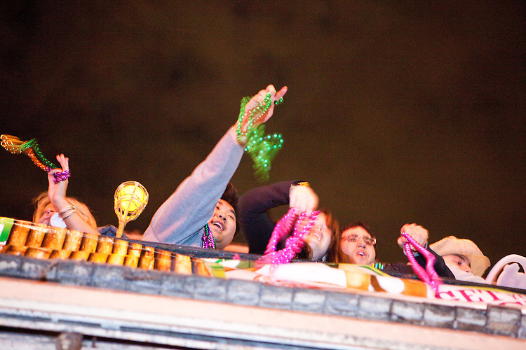 People perch on balconies to throw beads at pedestrians on Bourbon Street during Mardi Gras in New Orleans on February 14, 2010.