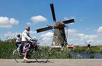 Oma fietst met kleinzoon langs een molen