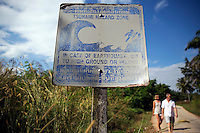 Tourists walk behind a faded sign warning of tsunami hazard in Khao Lak, in Thailand's Phang Nga province December 15, 2014. Ahead of the 10th anniversary of the disaster, which killed at least 226,000 people, experts and officials say key weaknesses remain across the region in a system designed to warn people of the next disaster, and get them to safety. Thailand prepares to mark the tenth anniversary of 2004 tsunami, the deadliest on the record, that killed at least 226,000 people in 13 Asian and African countries. REUTERS/Damir Sagolj (THAILAND)