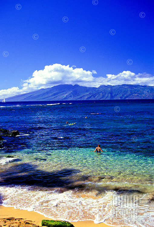 Kapalua Bay with a view of Molokai on a clear day with people snorkling