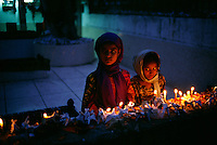 Young girls light candles at a mosque.