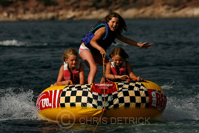 Young girls ride a water tube at Flaming Gorge Reservoir.