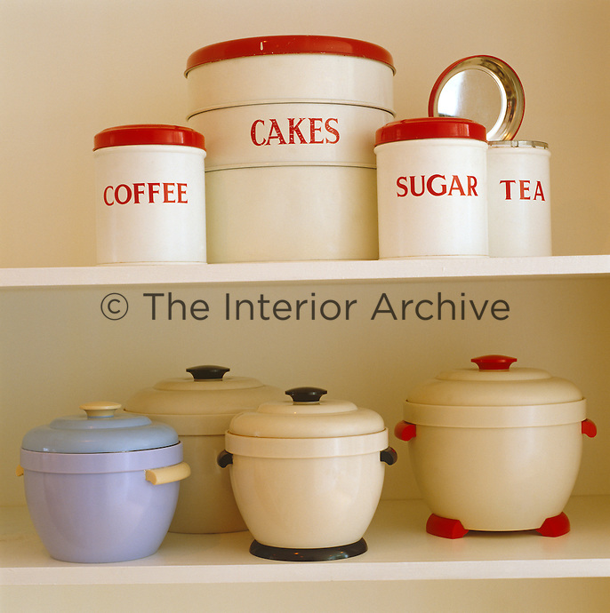 Retro enamel and Bakelite containers are displayed on a kitchen shelf