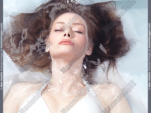 Natural look beauty face portrait of a young woman lying relaxed submerged in water with closed eyes. Beauty treatment concept in light colors.