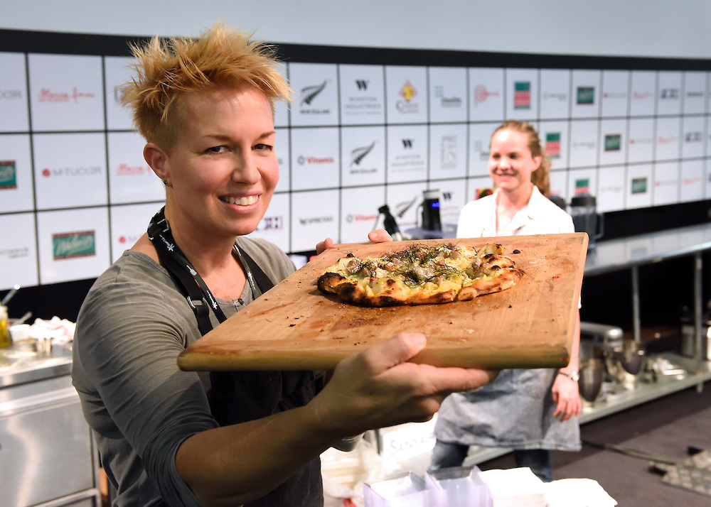 Chef Elizabeth Falkner holding a brick oven pizza fresh from the oven.