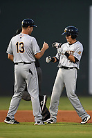Shortstop Diego Castillo (7) of the Charleston RiverDogs, right, bumps fists with Manager Patrick Osborn (13) after hitting a double in Game 2 of the South Atlantic League Southern Division Playoff against the Greenville Drive on Friday, September 8, 2017, at Fluor Field at the West End in Greenville, South Carolina. Charleston won, 2-1, and the series is tied at one game each. (Tom Priddy/Four Seam Images)