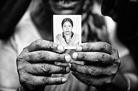 A woman shows a portrait of her missing daughter named Sokhina, believed trapped in the rubble following the collapse of an an eight-storey building Rana Plaza in Sava, near Dhaka, Bangladesh
