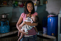 Irma Asoro, 29, holds her 4-month-old baby, Rashed James, who she has been feeding formula since he was 2 days old, in her rented home in an urban slum in Paranaque, Metro Manila, The Philippines on 19 January 2013. She thinks that formula is better for her baby even though the cost of formula and bottled water costs her more than double her rent, and she has to borrow from family and friends to pay for it. Photo by Suzanne Lee for Save the Children UK