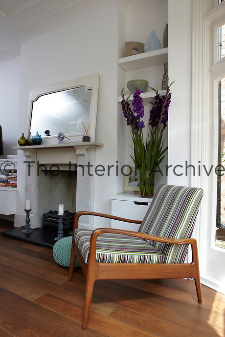 A traditional living room with a marble fireplace and a wooden floor. A retro style wooden armchair is placed in front of a built-in cupboard and shelving in a recess.