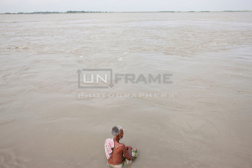 A man takes his bath in the River Padma. Every year in Bangladesh, millions of people are affected by river erosion that destroys home, farmland, communication infrastructure. In the last couple of days erosion by the Padma River has caused extensive damages to houses, agricultural lands, roads etc. In Dohar, lots of people lost their lands and homes due to Padma river banks erosion. Dohar, Dhaka, Bangladesh.
