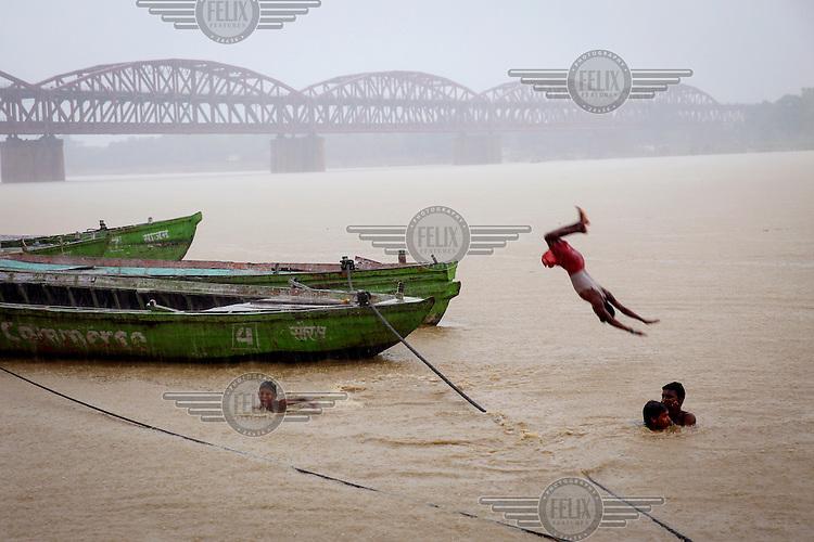 Children leap into the Ganges River near the Malviya Bridge.