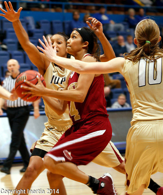 SIOUX FALLS, SD - MARCH 10:  Kailey Edwards #14 from Denver drives between a pair of defenders including Nicole Rogers #10 from IUPUI in the second half of their semifinal game at the 2014 Summit League Basketball Championships Monday at the Sioux Falls Arena(Photo by Dave Eggen/Inertia)