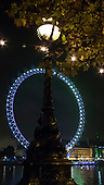 London, England. London Eye at night, with one of the iconic 'Dolphin' lamps.