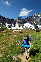 Woman hiking through alpine meadow, Washington's North Cascade Mountains in background, North Cascades National Park, Washington State, USA