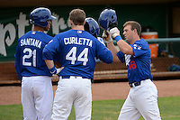 Kyle Farmer #18 of the Ogden Raptors is greeted at home plate by teammates Alex Santana #21 and Joey Curletta #44 after hitting a 3-run home run against the Idaho Falls Chukars at Lindquist Field on June 23, 2013 in Ogden, Utah. (Stephen Smith/Four Seam Images)