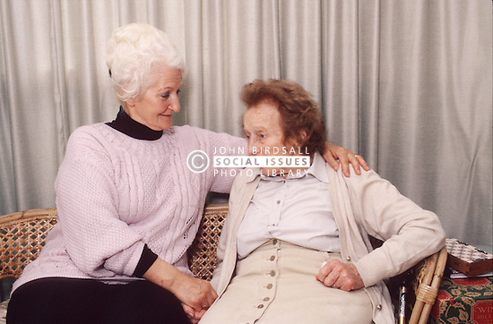Carer and elderly woman sitting together on sofa talking,