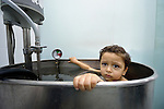 Three-year old Anas, who suffered a severe burn to her chest, sits in a therapeutic bath in the Al Ahli Arab Hospital in Gaza City. The Anglican Church-affiliated hospital is a member of the ACT Alliance.<br /> <br /> The 2014 war provoked serious damage to Gaza's health infrastructure. Seventeen hospitals, 56 primary health care facilities and 45 ambulances were damaged or destroyed. Sixteen health care workers were killed and 83, most of them ambulance drivers and volunteers, were injured.<br /> <br /> Parental consent obtained.