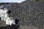 Piles of coal in a coal merchants yard, Rackhams, Wickham Market, Suffolk, England