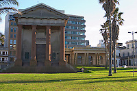 Holy Trinity Cathedral Anglican Church, Reconquista 522, Montevideo, in morning side light sunshine. Grass lawn in front with palms and modern buildings in the background. A single man sitting by the church. Montevideo, Uruguay, South America