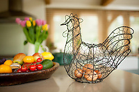 Eggs in wire hen ornament and bowl of fruit and vegetables in country kitchen in the Cotswolds, Oxfordshire, UK