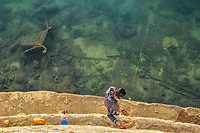 A man fishing with a handheld line from a sea wall, in the sea floor littered with assorted rubbish including a shopping cart and plastic pipes, by the seafront of the city of Piraeus near Athens, Greece, Mediterranean Sea, Atlantic Ocean
