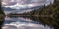 Pastel colours of dawn over Lake Matheson with reflections of Mt. Cook and Mt. Tasman, Westland Tai Poutini National Park, West Coast, UNESCO World Heritage Area, South Westland, New Zealand, NZ