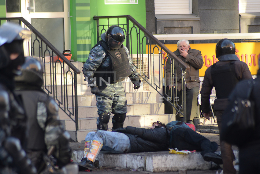 A Berkut policeman threats a couple of wounded protesters. Kiev, Ukraine