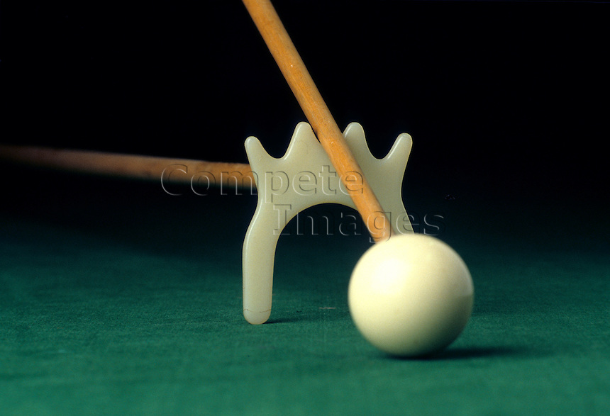 Close up of a white snooker ball with bridge and cue