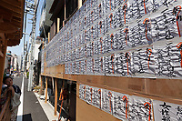 A woman looks at a board that shows the names of local people and business that donated to the Sanja matsuri, Asakusa, Tokyo, Japan. Sunday May 21st 2017. The Sanja matsuri (Three shrines festival) is one of the biggest Shinto festivals in Japan. It takes place for 3 days around the third weekend of May and features over 100 large and small mikoshi, or portable shrines, which are paraded around the streets of the historic Asakusa district in Tokyo. to bring blessings and good luck on the inhabitants. The events attracts up to 2 million visitors each year.