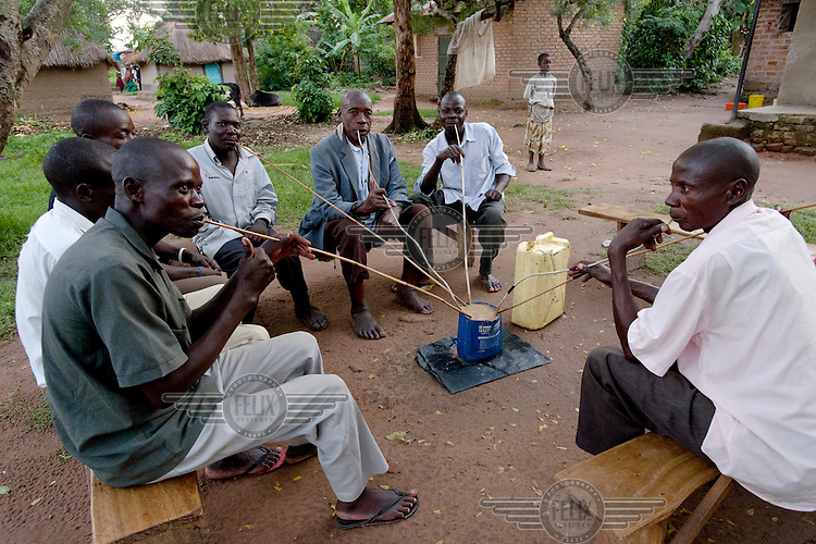 Men drinking ajono, a traditional beer made from millet or sorghum. Each person pays a fee per head, and drinks through a slender bamboo straw.