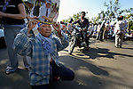"A man kneels as he participates in a vigil outside a Phnom Penh court on December 14, 2012, during a hearing in which judges denied an appeal by Mam Sonando, a Cambodian radio journalist and human rights activist. Mam Sonando was sentenced in October 2012 to 20 years in prison for ""insurrection,"" despite local and international calls for his release."