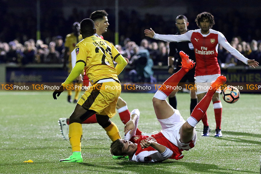 Rob Holding of Arsenal takes a tumble after a challenge from Sutton's Roarie Deacon during Sutton United  vs Arsenal, Emirates FA Cup Football at the Borough Sports Ground on 20th February 2017