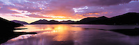 © David Paterson.Vivid sunset reflected in calm water, with range of hills (Ardgour) along horizon; Loch Leven, Lochaber district, west Highlands, Scotland...Keywords: sunset, evening, sundown, dusk, hills, range, lake, loch, fjord, Ardgour, Linnhe, Lochaber, Scotland, Highlands, peace, quiet