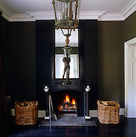 A bronze statue stands on the marble mantelpiece above a lit fire in the hall