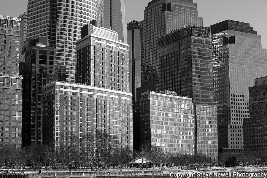 """Downtown"" Black and White Downtown Manhattan New York. The New World Trade Center Tower is the wide skyscraper in the left -middle of the photograph. I shot this Downtown Manhattan Skyline scene while on a boat tour in the days before the worst storm in 20 years blew in lasting three days. The strong winds made it difficult to stay warm, hold my camera stable on my monopod and stay out of the water spray from the waves created by the boat. The New World Trade Center tower was just finishing construction at the top and rises high above the other skyscrapers. During the storm Governors in surrounding states and New York banned driving personal vehicles on the public highways for a couple days.  Being from Lake Tahoe I came prepared for the weather and was excited to capture New York City and Central Park with fresh snow. The incredible skyline of Manhattan was breathtaking. Growing up in California, visiting San Francisco as an adult regularly and shooting it many times as a professional photographer didn't prepare me for the magnitude of the impressive size and quantity of the buildings and skyscrapers that form the skyline of Manhattan. My hat is off to the Architects and Engineers who contributed to building the touted greatest city on Earth. Black and white photography is still my favorite so you will see many images offered in Color and BW."
