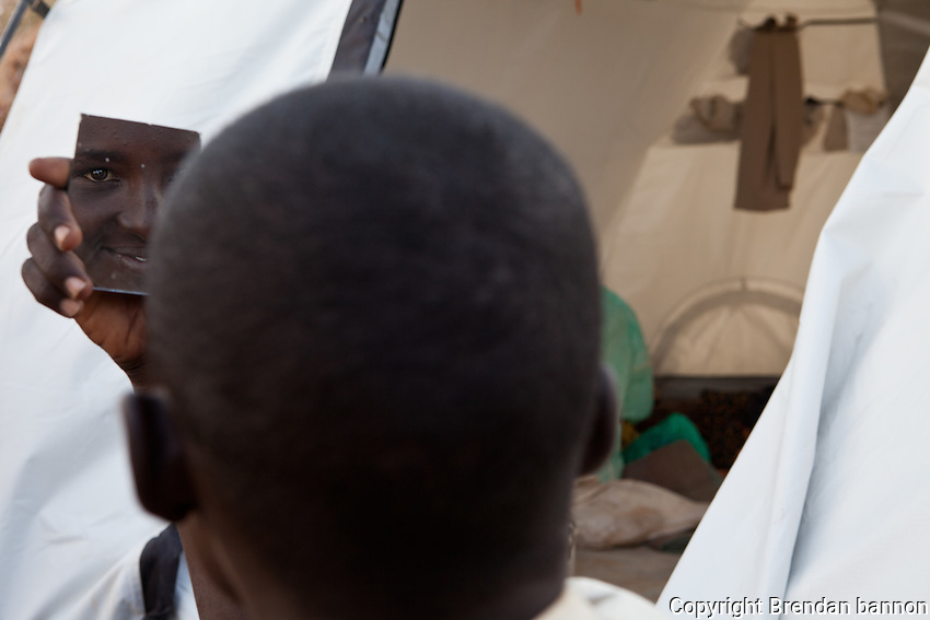 A somali refugee boy looking at himself in the mirror in Ifo 2, part of the world's largest refugee camp near Dadaab, Kenya. October 2011.