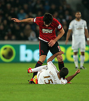 Wayne Routledge of Swansea brought on the ground by Claudio Yacob (TOP) of West Bromwich Albion during the Barclays Premier League match between Swansea City and West Bromwich Albion played at the Liberty Stadium, Swansea on December 26 2015