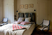 In the master bedroom a pair of built-in wardrobes flank the bed with an unusual headboard imaginatilvely constructed from restored wooden palettes