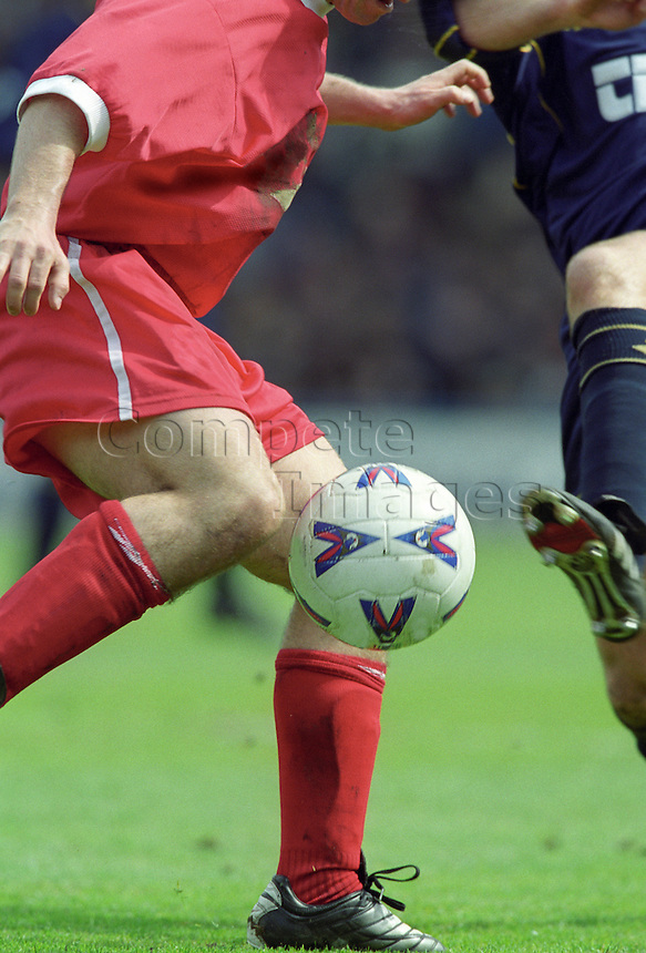 Two football players go for the ball