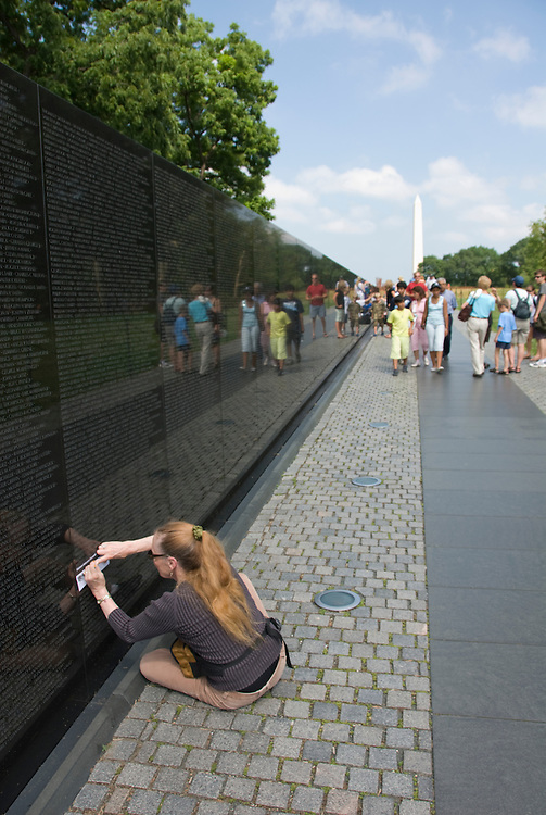 Washington DC; USA: The Vietnam Veterans Memorial on the Mall.  Doing a rubbing of a name on the wall of dead soldiers..Photo copyright Lee Foster Photo # 8-washdc82982