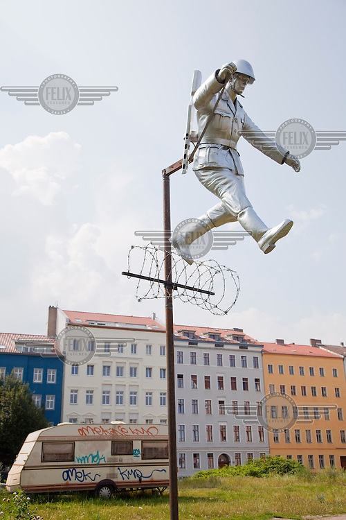 """Sculpture recreating the famous photograph of an East German border guard jumping to freedom over the Berlin Wall in its early days of construction when it was little more than a barbed wire fence. This is near the exact spot on Bernauer Strasse where the photo was taken and where many desperate scenes took place in 1961 as people jumped from the windows of their houses that stood on the edge of the Wall into West Germany. The green area is the former """"death strip"""" that was created on the eastern side of the Wall once it was erected making it more difficult to escape to the West."""