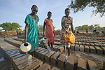 Women water newly formed concrete blocks to keep them from drying too quickly at the Loreto School in Rumbek, South Sudan. The school is run by the Institute for the Blessed Virgin Mary--the Loreto Sisters--of Ireland. The blocks are being used to construct new classrooms.