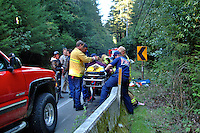 Paramedics and volunteer firefighters treat the victim of a motorcycle accident and get ready to transport her in Camp Meeker and Occidental California
