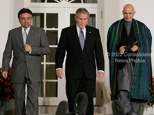 WASHINGTON - SEPTEMBER 27:  (AFP OUT) US President George W. Bush (M) flanked by Afghanistan President Hamid Karzai (R) and Pakistani President Pervez Musharraf (L) walk into the Rose Garden before delivering remarks at the White House September 27, 2006 in Washington. DC. Bush is hosting a meeting between the two leaders. (Photo by Mark Wilson/Getty Images) *** Local Caption *** Hamid Karzai;George W. Bush;Pervez Musharraf