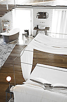 A vintage-style slipper bath has been installed in a corner of the bedroom where wood floor changes to ceramic tiles