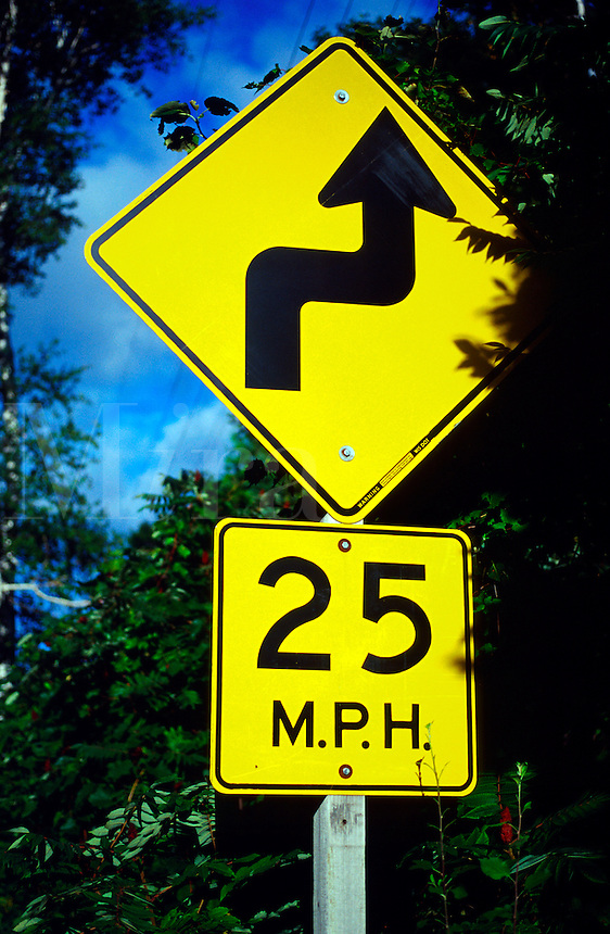 Bright yellow traffic sign indicates a safety warning for travel at 25 M.P.H. and a curved arrow symbolizing a winding road.